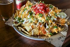 Bar-B-Q Nachos at Jim 'N Nicks Bar-B-Q   Multiple locations The chips here get topped with mixed lettuce, smoked tomato salsa, queso sauce, sour cream, spicy Serrano peppers, shredded cheddar and barbecue sauce, plus your choice of the restaurant's smoked meats, like pulled pork, vinegar-laced Carolina-style pork, beef brisket and turkey.   - Delish.com