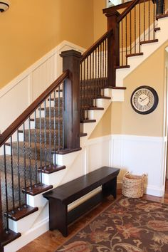 like the white wood paneling- plus maybe easier to keep clean than painted wall on the stairs? dark wood and white together with wrought iron spindles