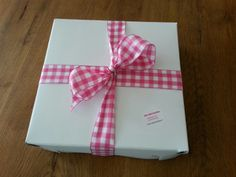 De Cheesecake wordt afgeleverd in een doos met een mooie strik eromheen.