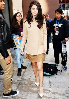 Selena Gomez wears a camel-color turtleneck, miniskirt, and ankle-strap pointed-toe pumps