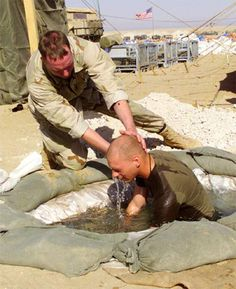 A chaplain with the 7th Marine Regiment baptizes a Marine at the Camp Ripper Chapel February 23, 2003 during Operation Enduring Freedom. Photo credit: U.S. Marines