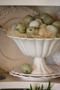 pretty cupboard of white plates, silver and Decorative Eggs