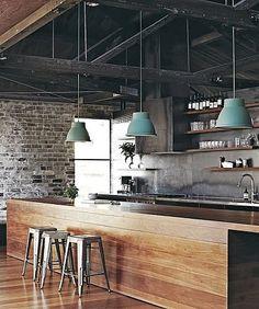 Le bois s'étend du parquet au plan de travail dans cette cuisine à la déco indus' discrète. Le mur en briques apparentes au fond de la pièce contraste avec la structure du plafond en acier noir. Les quelques accessoires se chargent d'accentuer le design usine. Les trois tabourets Tolix couleur métal amènent la touche de vintage tandis que la note de couleur est apportée par les suspensions bleu gris.