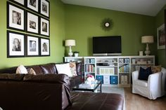 #livingroom  dark brown sofa, green wall, hint of white