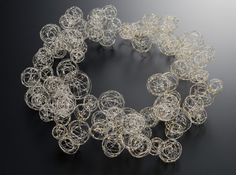 Knitting, weaving and crocheting stainless steel, silver and gold wire into net-like structures, Haruko Sugawara creates delicate, often hollow jewelry. The artist applied cloisonne and heat to some of the pieces in the Crochet collection, Pebbles and Bubble series, adding color and depth to these gossamer works. - See more at: http://dailyartmuse.com/page/2/?s=wire#sthash.PhP6zNSB.dpuf