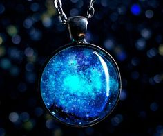 Carry the majesty of the cosmos on you with this glow in the dark galaxy necklace. Handmade upon request, the chain can be adjusted to your desired length while the pendant comes filled with a powder that glows in the dark after charging under UV light.