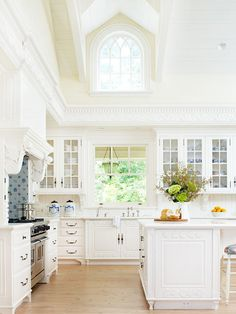 Introduce country French to your kitchen with c'est magnifique details and a crisp color scheme. In this kitchen, steel hardware inspired by French designs crowns cabinets with classic Gustavian detailing. Charming dormers and arched Gothic windows draw the eye up to the beamed cathedral ceiling. To easily achieve a country French look, consider a blue-and-white color scheme and change out small things, such as hardware or light fixtures, for items that have a definitively French look.