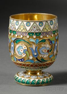 Russian Gold-washed Silver and Cloisonne Enamel Footed Cup, Moscow, 1908-17, purveyor to the tsar maker's mark partially obscured but possibly Ovchinnikov, slightly tapered cylindrical cup with geometric pastel and floral cloisonne enameling, with small overpainted gilt accents, on short stem with spreading foot with teal green Vitruvian scroll rim.