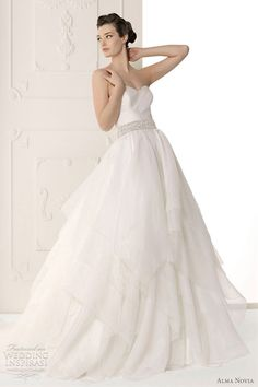 Sutil strapless ball gown with tiered skirt, waist adorned with crystal embellished sash.