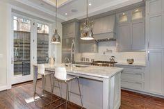 Серая кухня в интерьере: 75+ избранных классических и современных дизайнерских решений http://happymodern.ru/seraya-kuxnya-v-interere-foto/ Обилие встроенных источников искусственного освещения, длинные подвесные лампы и естественный свет, идущий со стеклянных дверей, в сочетании со светло-серой отделкой кухни