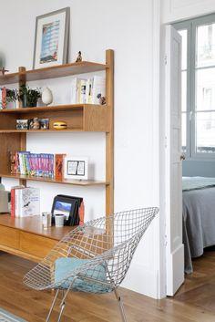 La bibliothèque au look vintage de Maisons du monde attire l'œil avec sa silhouette géométrique, tandis que le fauteuil Bertoia donne une touche design chic et intemporelle.