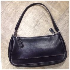 Black Leather Coach Purse Used only a few times. Silver hardware and zipper. Perfect for when you only want to carry a few things with you! Coach Bags