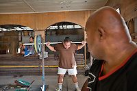 Gerard advising Roland Raboe..Gerard Jones (R, age 47, super class, 143 kg), is the national trainer..Nauru's Weightlifting Gym in Aiwo District (Aiwo's Boys Gym). Girls and boys train here every day starting at 5pm. Nauru's weightlifting champions (including the President of Nauru) have won several gold medals at the Commonwealth Games. Weightlifting is the pride of the nation..Although Nauru is the world's fattest country, with 94% of its population being overweight,