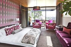 Check out this eclectic master bedroom with a pink-and-gray patterned wall and comfortable purple couch on HGTV.com.