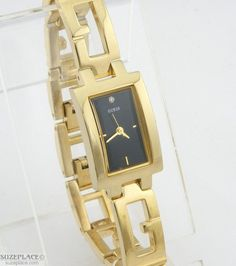 Ladies Guess Watch with gold tone band & black dial. SuzPlace.com