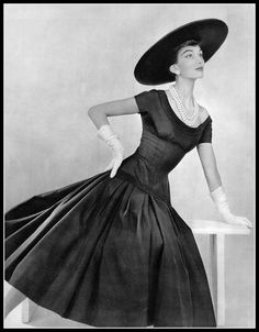 Marie-Hélène Arnaud in navy blue alpaca wool dress, low scooped neckline on bodice that extends to the hips, full skirt gathers from decorative ribbon, by Jacques Fath, photo by Pottier, 1955