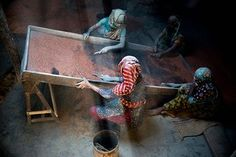 Women, in Bangladesh, working under a tin shade roof.