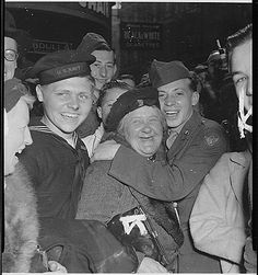 Jubilant American soldier hugs English woman and victory smiles light the faces of happy service men and civilians at Piccadilly Circus, London, celebrating Germany's unconditional surrender. England, May 7, 1945.