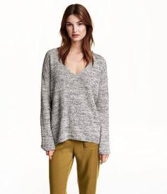 CONSCIOUS. En v-ringet, strikket genser i myk bomullsblanding. Den har lange ermer og et noe lengre bakstykke. Bomullen i genseren er resirkulert.