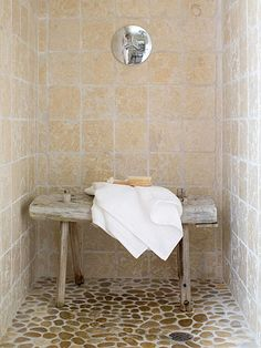 A walk-in shower is lined with tumbled-marble tile for earthy elegance. The raised texture of the pebble floor is naturally slip-proof. A weathered wood bench provides easy-access storage for toiletries. Editor's Tip: Worn wood pieces, such as this bench, only get more character with age so they can be used anywhere, even the shower.