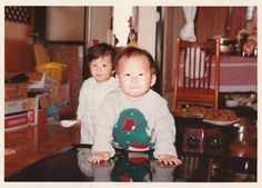 When I was young. With cousin Min-gyu wearing Christmas sweater. On the behind table are pancakes. Min-gyu puts both hands on the table.