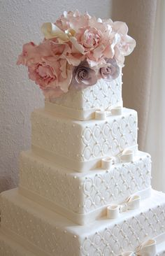 Classic white wedding cake with bows and sugar flowers.
