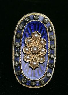 "Very fine Georgian blue enamel mine cut diamond ring. This ring is not hallmarked but tests with acids for 18K yellow gold. The top has tiny seed pearls (tears) and 18 rose cut diamonds. The cobalt blue enamel is champleve enamel, where the design behind the enamel was etched by hand and then the translucent enamel was placed over it. On the inside there is hand engraving that says "" Emily Dawson Obt. 6th Mar 1789""."