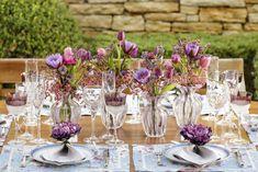 Mesa com tons de azul e roxo para um clima alegre aconchegante! Flores ao centro da mesa em vasos de Murano by Paula Bassini e jogos americanos florais by Couvert foram nossas maiores inspirações para essa produção!