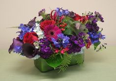 This arrangement doesn't just have cool colors, it's horizontal design lends itself well to a dining table or sideboard. - cala lilies, stock, delphinium, gerberas, roses and hydrangea
