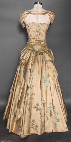 """BACK GOLD BROCADE EVENING GOWN, 1940s Go Back April 8, 2015 NYC New York City Gold silk satin w/ white carnation & green foliage brocade, 2 panels attach to halter bodice & tie at BW, voluminous circle skirt, B 35"""", W 27"""", CFL 50"""", Hem Circumference 146"""", (bust & waist let out, few small stains) very good. Museum De-Accession."""