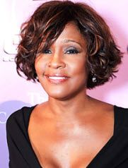 Whitney Houston- Dark brown with caramel highlights bob haircut with tousled loose curls and side swept bangs hairstyle