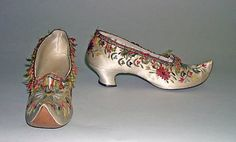 Shoes by Hellstern & Sons, 1870s, the Met Museum. These must have been part of a fancy dress ensemble. The turned-up toes were an odd fashion statement of the day, but look at the trim! The embroidery and fringe go all the way around. More images at link.