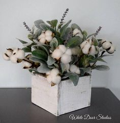 Cotton stems and white wood are staples of farmhouse style decor. Paired with soft green lambs ear stems and sprigs of lavender, this cotton arrangement is rustic, farmhouse perfection. Handcrafted with natural cotton boll stems, charming artificial lambs ear greenery and lifelike