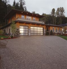 The early morning sunrise reflects off of the Clopay frosted glass garage doors on this rustic modern home. www.clopaydoor.com