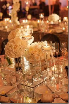 white roses and high candles wedding centerpiece I love the reflection festival going on here. So pretty!