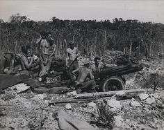 """75mm Howitzer, Peleliu, 1944  """"Present for the Japs-Marines manning a 75-mm, pack howitzer, hurl shells at enemy ridge positions on Peleliu, from hastily-dug emplacements."""""""