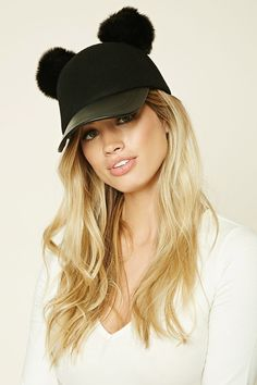 A wool baseball cap featuring faux fur pom-poms and a faux leather brim.