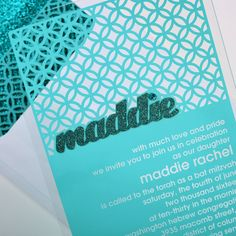 This infinite-circle geometric motif Bat Mitzvah invitation is on clear Plexi with a Prussian blue laser cut name applique embellished with a rhinestone. Blanketing the Plexi using both teal silk screen and thermography pattern, it reveals the wording as if it were etched out of the Plexi. Choose the Prussian blue envelope lining for a pop!