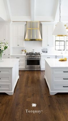 Double kitchen islands, a mixed-metal range hood, brass accents, and Cambria quartz countertops create the ultimate in kitchen glamour. This bright white kitchen space features Torquay from Cambria's Marble Collection, a high-performing marble alternative that won't stain or scratch with everyday use. Learn more tips for creating a luxurious kitchen space. #MyCambria