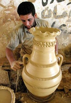 A Palestinian pottery worker is putting final touches on a earthenware vase at his traditional pottery  factory in the West Bank city of Hebron, October 7, 2003