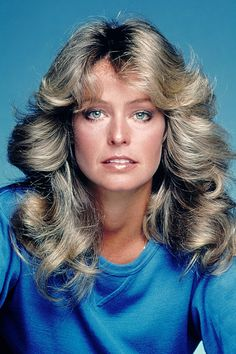 """American Hustle Hair: A Glam Guide to '70s Hairstyles #refinery29 http://www.refinery29.com/70s-hairstyles#slide7 Farrah Fawcett People, THIS is the '70s style that launched a million posters and inspired a decade of copycats. The Charlie's Angels star's flipped-out style was made even more marvelous by her own natural texture. """"Her hair was actually curly, and the look was achieved by this very thick, layered cut coupled with blowing and curling her hair away from her face,"""" says Josh."""