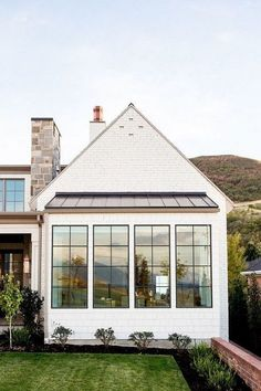 Modern farmhouse exterior with white painted brick and black steel windows.