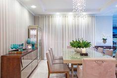 Sala com buffet espelhado, mesa com tampo de vidro branco e cortinas e tecidos pesados compõem esta sala de jantar projetado pelo escritório OMK Arquitetura em Maringá (PR).