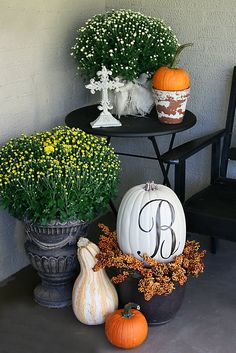 Black flower pot with some fall color berry picks... white pumpkin sitting in pot with black P.  Place by front door!