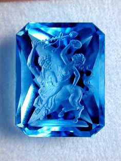 Treated Blue Topaz with an intricate Inatglio carving showing a centaur robbing a woman. The motif is from an ancient carving.