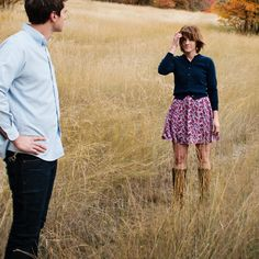Awesome engagement photo, girl and boy standing in a field looking at each other