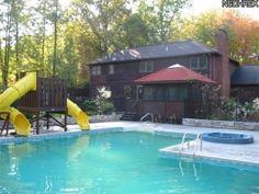 In Ground L-Shaped Swimming Pool wrapped in Stone & Wrought Iron Fence