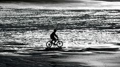 Young child cycling on St Bees beach . Silhouette . Cumbria .  www.eternityimages.co.uk