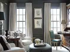 transitional design: dark gray walls, wainscoting gray, white/cream curtains, and rustic/industrial furniture, and tufted seat/ bench