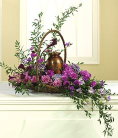 Purple lilies, roses and orchids in sympathy arrangement